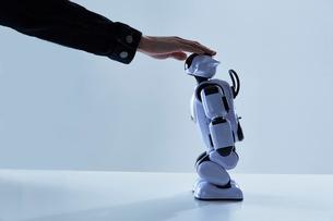 ロボットの頭を撫でる人間の手の写真素材 [FYI02825247]