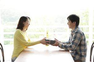夫にプレゼントを贈る30代女性の写真素材 [FYI02825250]