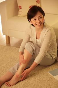 夜に脚のケアをするミドル女性の写真素材 [FYI02825254]