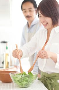 キッチンでサラダを作る若い女性の写真素材 [FYI02825277]