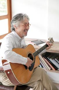 ギターを弾くミドル男性の写真素材 [FYI02825379]