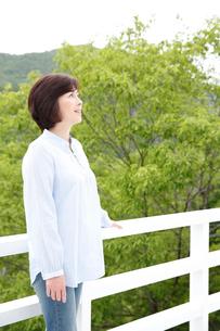新緑を背にたたずむミドル女性の写真素材 [FYI02825410]