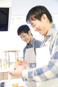 料理教室で調理する2人の30代男性の写真素材 [FYI02825415]