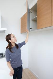 真新しいキッチンをチェックする若い女性の写真素材 [FYI02825421]