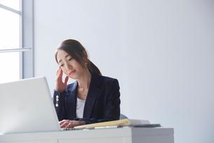 職場のデスクでパソコンを見て暗い表情をする女性の写真素材 [FYI02825432]