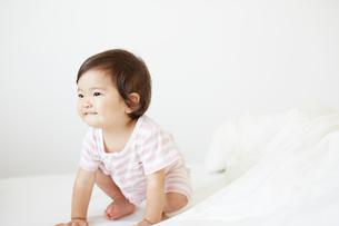 ベッドの上でしゃがみこんでいる赤ちゃんの写真素材 [FYI02825435]