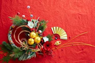 赤い和紙上の水引と花の正月飾りと締縄の写真素材 [FYI02825440]