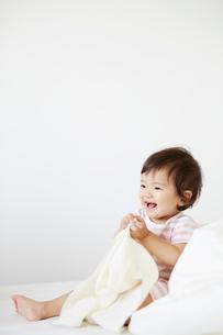 ベッドの上でタオルを持って笑っている赤ちゃんの写真素材 [FYI02825459]