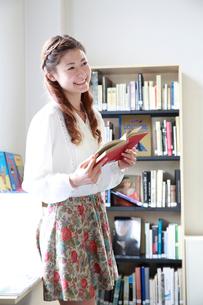 図書室で微笑む女子大学生の写真素材 [FYI02825492]