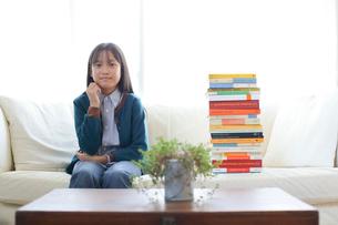 山積みの本とソファで微笑む少女の写真素材 [FYI02825503]