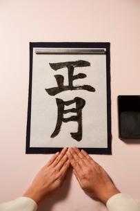 薄いピンクの背景の書き初めと揃えた女性の手の写真素材 [FYI02825530]