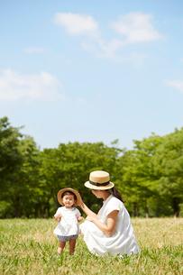 芝生の上でお揃いの帽子を被る母と娘の写真素材 [FYI02825532]