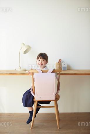 勉強スペースで振り向いて笑う小学生の女の子の写真素材 [FYI02825534]