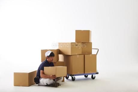 白バックの空間で台車の荷物を落として座り込む作業着の男性の写真素材 [FYI02825542]
