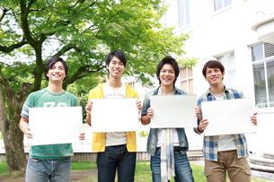 メッセージボードを持つ4人の若い男性の写真素材 [FYI02825667]