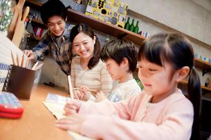 勉強する兄妹を見守る両親の写真素材 [FYI02825856]