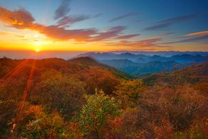 旧碓氷峠見晴台から望む妙義山などの山並みと紅葉の樹林と朝日の写真素材 [FYI02826157]
