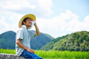 水田の近くで休憩をする男性の写真素材 [FYI02826185]