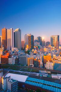 新宿のビル群と西武新宿駅と特急スーパーあずさと反射する朝日の写真素材 [FYI02827427]