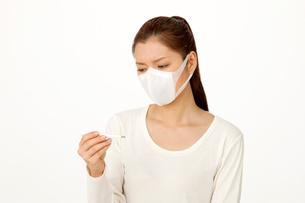 マスクをして体温計を見る女性の写真素材 [FYI02828546]