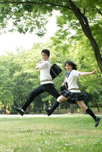 公園でジャンプする高校生カップルの写真素材 [FYI02828615]