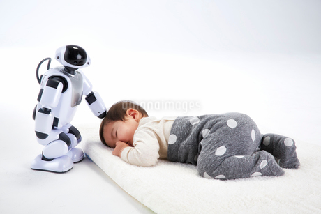 お昼寝する赤ちゃんを見守るロボットの写真素材 [FYI02828616]
