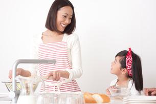 キッチンで料理する母と女の子の写真素材 [FYI02828678]