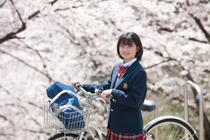 桜と自転車の女子高生の写真素材 [FYI02828683]