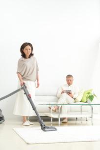 掃除機をかける中高年女性とソファに座る男性の写真素材 [FYI02828729]