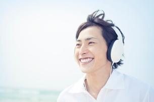 ヘッドフォンをつけた笑顔の男性の写真素材 [FYI02828777]