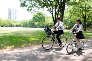 自転車に乗って走る高校生カップルの写真素材 [FYI02828835]