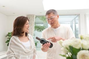 ワインの銘柄を見る中高年夫婦の写真素材 [FYI02828844]