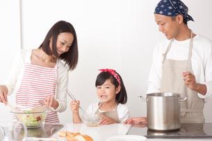 キッチンで料理する両親と女の子の写真素材 [FYI02828850]