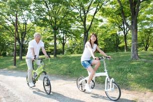 自転車に乗って走る父と娘の写真素材 [FYI02828858]
