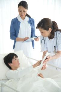 病院ベッドの男の子を診察する女医と看護師の写真素材 [FYI02828895]
