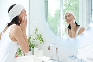 洗面台の鏡を見てお化粧をする女性の写真素材 [FYI02828903]