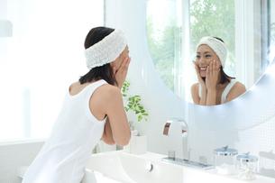 洗面台の鏡を見てお化粧をする女性の写真素材 [FYI02828904]