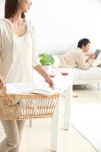 洗濯物を運ぶ女性とソファの男性夫婦の写真素材 [FYI02828918]