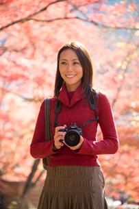 紅葉をカメラで撮影する女性の写真素材 [FYI02828933]