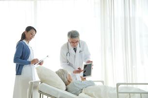 病院ベッドの老人を診察する医者と看護師の写真素材 [FYI02828969]