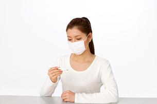 マスクをして体温計を見る女性の写真素材 [FYI02828985]