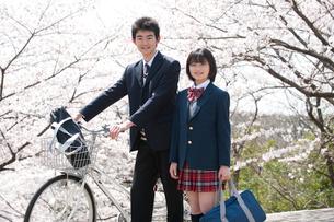 桜と自転車の高校生男女の写真素材 [FYI02829016]