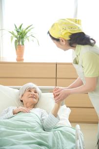介護ベッドの老人の手を握る介護ヘルパーの写真素材 [FYI02829083]