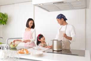 キッチンで料理する20代夫婦と女の子の写真素材 [FYI02829136]