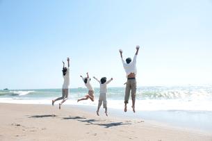 海辺でジャンプする家族の写真素材 [FYI02829197]