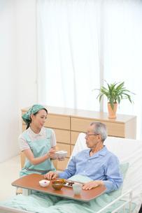 介護ベッドの老人に食事をさせる介護ヘルパーの写真素材 [FYI02829206]