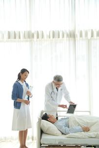 病院ベッドの老人を診察する医者と看護師の写真素材 [FYI02829237]