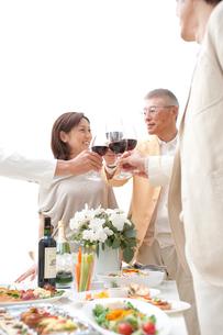 赤ワインで乾杯する中高年夫婦とホームパーティーのお客様の写真素材 [FYI02829254]