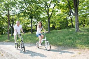 自転車に乗って走る父と娘の写真素材 [FYI02829258]