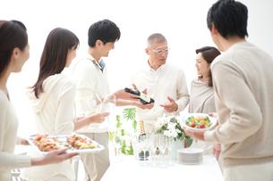 ワインの銘柄を見る中高年夫婦とホームパーティーのお客様の写真素材 [FYI02829296]